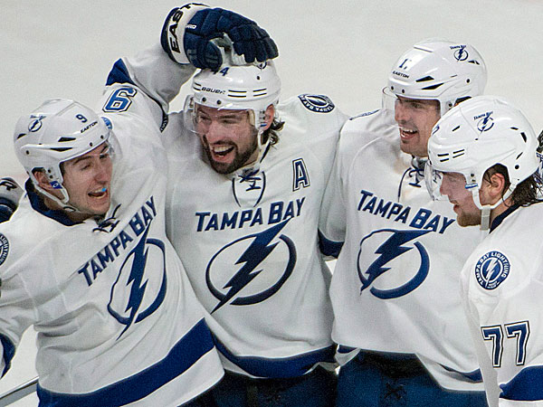 Lightning Nate Thompson, second from left, celebrates his overtime goal against the Montreal Canadiens in an NHL game in Montreal, Saturday, Feb. 1, 2014. The Lightning won 2-1 in overtime. (AP Photo/The Canadian Press, Peter McCabe)