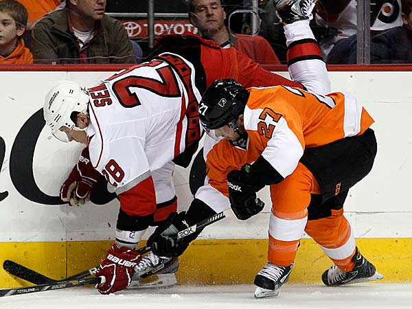 Carolina Hurricanes´ Alexander Semin (left) and Philadelphia Flyers´ Bruno Gervais dig for the puck along the boards in the first period of an NHL hockey game on Saturday, Feb. 2, 2013, in Philadelphia. (Tom Mihalek/AP)