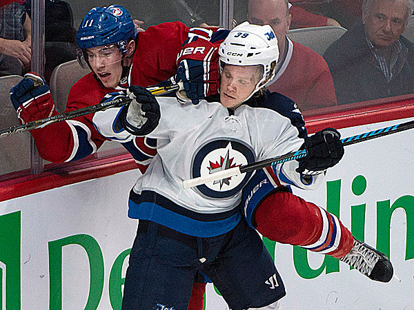 The Canadiens´ Brendan Gallagher is put up onto the boards by the Jets´ Tobias Enstrom. (Peter Mccabe/The Canadian Press/AP)