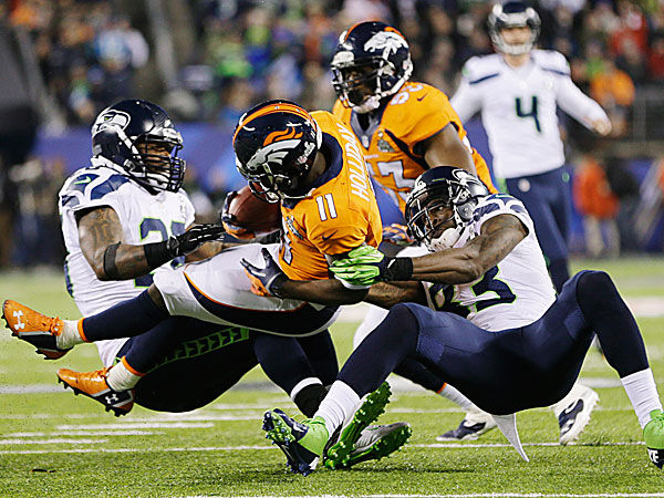 The Broncos´ Trindon Holliday is brought down by the Seahawks´ Michael Robinson and Ricardo Lockette. (Mark Humphrey/AP)