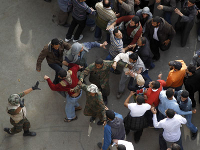 Soldiers protect a suspected pro-government supporter, bottom left in red, near Cairo´s main square on Thursday. (AP Photo / Tara Todras-Whitehill)