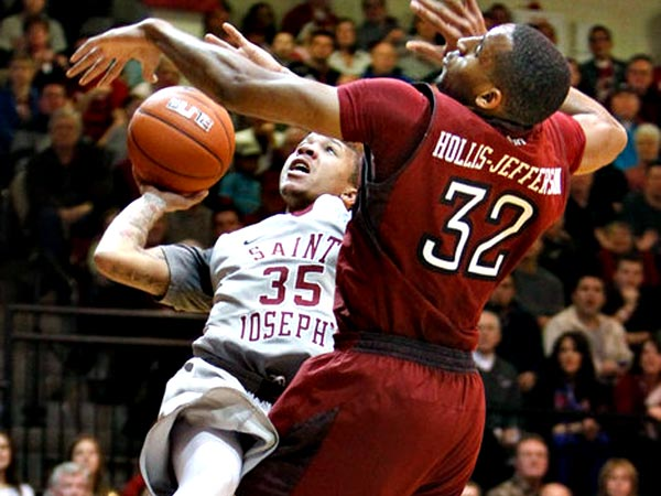 Despite foul from Temple´s Rahlir Hollis-Jefferson, St. Joe´s Carl Jones manages to score. (Ron Cortes/Staff Photographer)