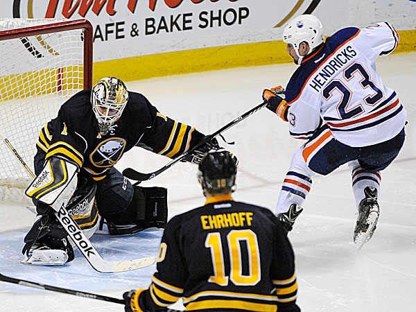 Sabres goaltender Jhonas Enroth and defenseman Christian Ehrhoff can´t stop Oilers center Matt Hendricks. (Gary Wiepert/AP)