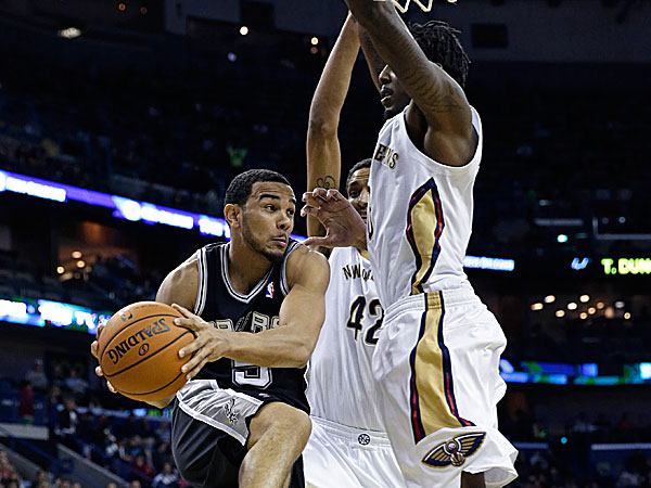 Spurs point guard Cory Joseph passes around Pelicans center Alexis Ajinca and Al-Farouq Aminu. (Gerald Herbert/AP)