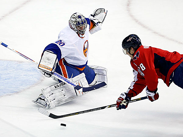 Capitals right wing Alex Ovechkin falls as he tripped with Islanders goalie Evgeni Nabokov defending. (Alex Brandon/AP)