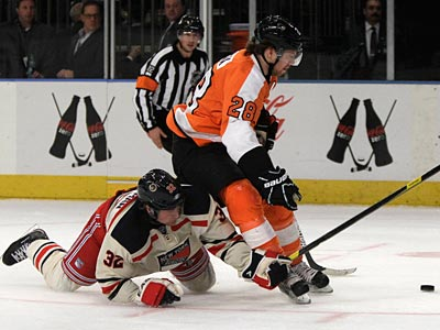 Claude Giroux and Anton Stralman battle for the puck in the first period. (Kathy Willens/AP)
