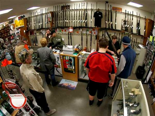 Customers line up at the gun counter at Duke´s Sport Shop in New Castle, Pa., in January. A new report says more guns are reported lost or stolen from Pennsylvania gun dealers than anywhere else in the country. (AP Photo/Keith Srakocic, File)