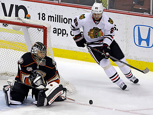 Ducks goalie Jonas Hiller deflects the puck as Blackhawks center Michal Handzus skates past. (Reed Saxon/AP)