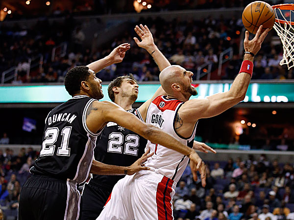 Wizards center Marcin Gortat drives to the basket between Spurs forward Tim Duncan and center Tiago Splitter. (Alex Brandon/AP)