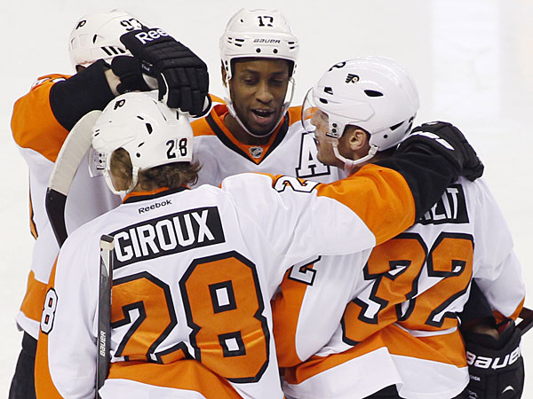 Wayne Simmonds, celebrates with teammates, from left, Jakub Voracek, Claude Giroux (28) and Mark Streit (32) after scoring against the San Jose Sharks during the first period of an NHL hockey game, Monday, Feb. 3, 2014, in San Jose, Calif. (George Nikitin/AP)