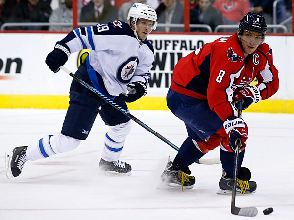 Capitals right wing Alex Ovechkin  looks to pass as Winnipeg´s Tobias Enstrom closes in. (Alex Brandon/AP)