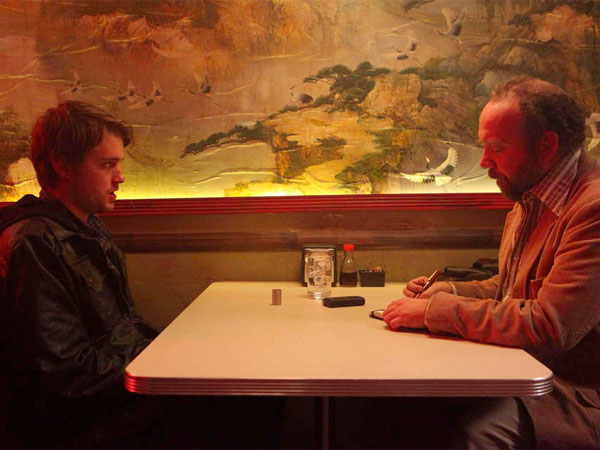 "Chase Williamson (left) as Dave Wong is interviewed by a journalist played by Paul Giamatti in ""John Dies at the End."""