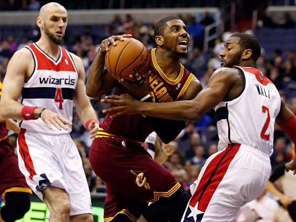 Cavaliers guard Kyrie Irving (2) looks to shoot between Washington Wizards center Marcin Gortat (4), from Poland, and guard John Wall (2) in the first half of an NBA basketball game on Friday, Feb. 7, 2014, in Washington. (Alex Brandon/AP)