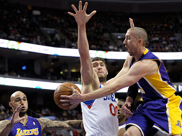 The Lakers´ Steve Blake, right, passes the ball to Robert Sacre, left, as Philadelphia 76ers´ Spencer Hawes, center, defends during the first half of an NBA basketball game on Friday, Feb. 7, 2014, in Philadelphia. (Michael Perez/AP)