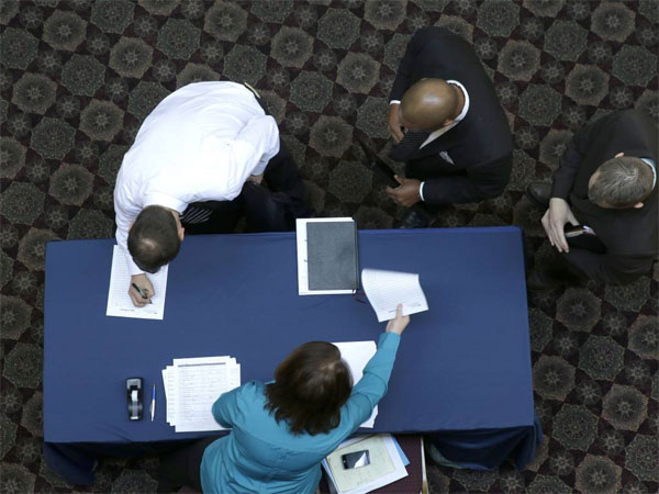 FILE - In this Wednesday, Jan. 22, 2014, file photo, job seekers sign in before meeting prospective employers during a career fair at a hotel in Dallas. The Labor Department reports on the number of people who applied for unemployment benefits for the first week of February on Thursday, Feb. 6, 2014. (AP Photo/LM Otero, File)
