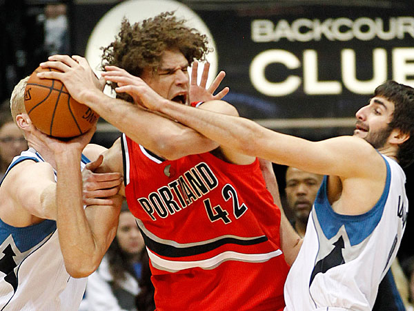 The Timberwolves´ Ricky Rubio, right, and Chase Budinger, left, foul Portland Trail Blazers center Robin Lopez in the fourth quarter of their NBA basketball game won by the Trail Blazers 117-110 on Saturday, Feb. 8, 2014, in Minneapolis. (Andy Clayton-King/AP)