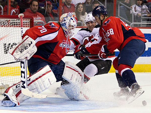 Capitals goalie Braden Holtby, left, and defenseman Connor Carrick, right, battle New Jersey Devils right wing Stephen Gionta during the first period of an NHL hockey game on Saturday, Feb. 8, 2014, in Washington. (Evan Vucci/AP)