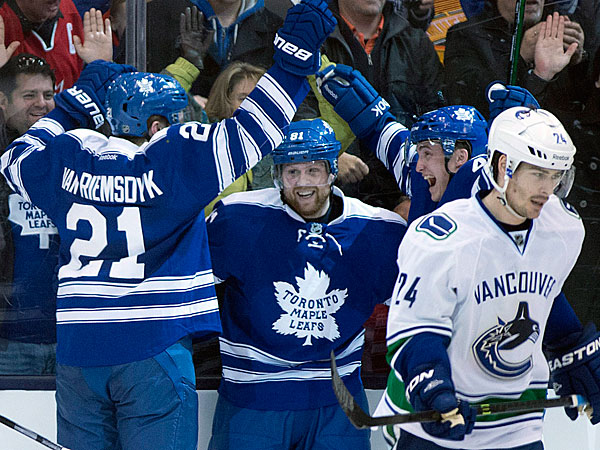Toronto Maple Leafs´ James van Riemsdyk, left, celebrates his goal with teammates Tyler Bozak and Phil Kessel, center, as Vancouver Canucks defenseman Raphael Diaz (24) skates away during the third period of an NHL hockey game, Saturday, Feb. 8, 2014 in Toronto. (AP Photo/The Canadian Press, Frank Gunn)