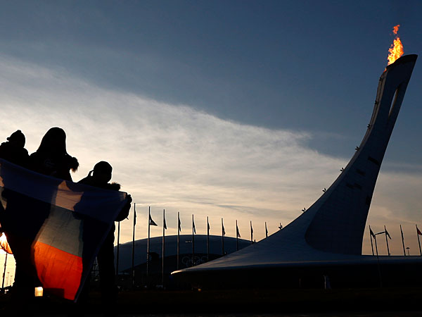A woman and two children hold a Russian flag while posing for a photograph in front of the Olympic cauldron during the 2014 Winter Olympics, Saturday, Feb. 8, 2014, in Sochi, Russia. (Julio Cortez/AP)