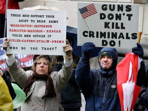 Betty and Robert Bailey of Millstone Township, N.J., hold signs during a Second Amendment rally outside the Statehouse in Trenton. (Mel Evans / Associated Press)