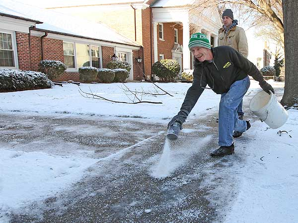 Chris McArdle, of McCardle Landscaping, looks like he is bowling in February 2013 as he spreads salt on the sidewalk of the First United Methodist Church of Media, Pa. (Michael Bryant / Staff Photographer)