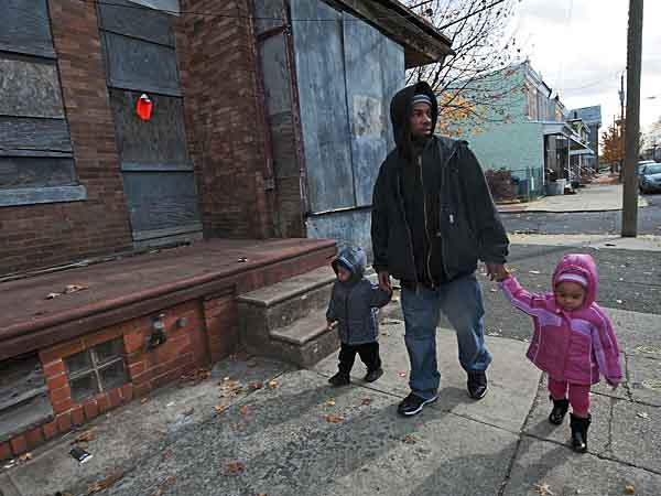 In this November 2012 photo, Charley Shambry, who does day care for two-year old twins Ryan (left) and Raniya Shambry, with the children on his Camden block, where it´s difficult to take a walk because of drug activity.  APRIL SAUL / Staff Photographer