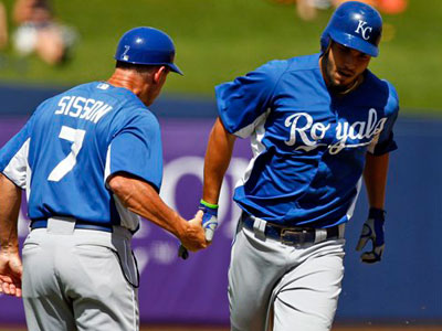 Kansas City Royals third base coach Doug Sisson, left, greets Eric Hosmer as he rounds the bases after hitting a two-run home run during the third inning of a spring training baseball game against the Milwaukee Brewers in Phoenix, Tuesday, March 27, 2012. (AP Photo/Chris Carlson)
