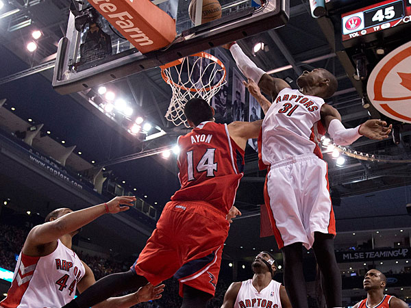 Raptors guard Terrence Ross (31) tries to guard as Atlanta Hawks center Gustavo Ayon (14) lays up for a basket during first-half NBA basketball game action in Toronto, Wednesday, Feb. 12, 2014. (AP Photo/The Canadian Press, Frank Gunn)