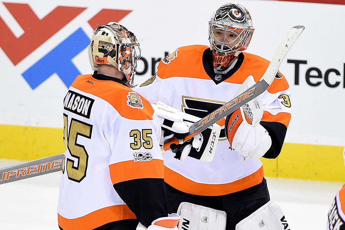 Philadelphia Flyers goalie Steve Mason (35) skates toward the bench as goalie Michal Neuvirth, right, of the Czech Republic, greets him after he was pulled during the third period of an NHL hockey game against the Washington Capitals, Sunday, Jan. 15, 2017, in Washington.