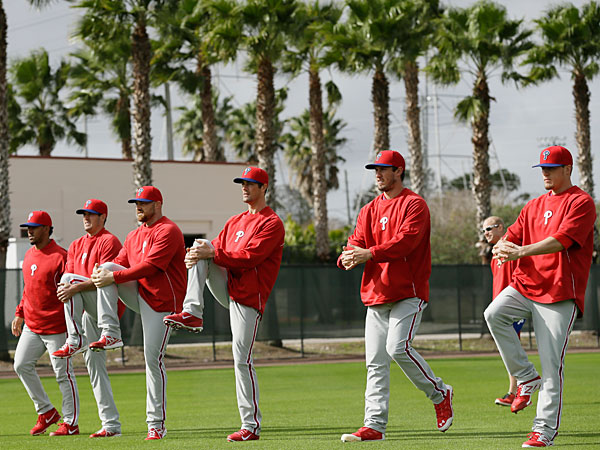 Phillies players stretch in the outfield during spring training baseball practice Thursday, Feb. 13, 2014, in Clearwater, Fla. (Charlie Neibergall/AP)
