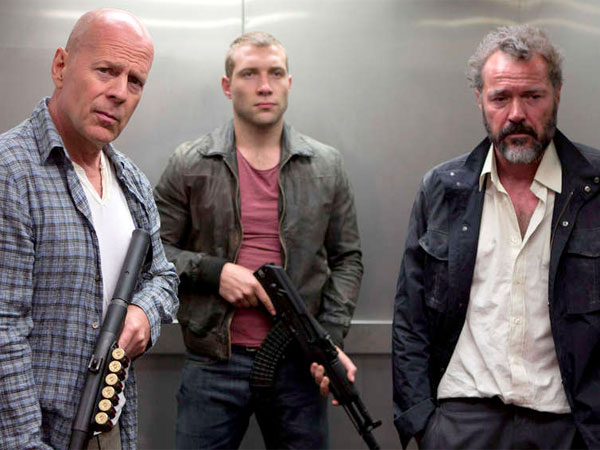 Bruce Willis (left) again packs plenty of firepower, this time while he helps his son, played by Jai Courtney (center), protect a Russian witness, played by Sebastian Koch.