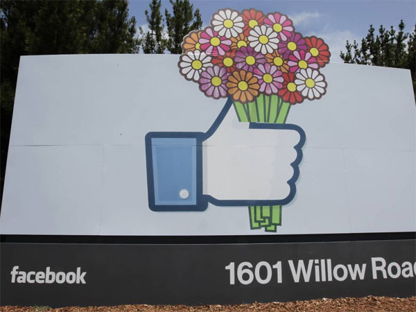 FILE - In this Sunday, May 13, 2012, file photo, flowers are added to a Facebook sign in front of Facebook headquarters in Menlo Park, Calif.  On Tuesday, Feb. 4, 2014, Facebook celebrates 10 years since its inception. (AP Photo/Paul Sakuma, File)