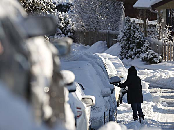 A person removes snow from a car in the Philadelphia suburb of Wynnewood, Pa. Friday,  Feb. 14, 2014.  Commuters faced slick, slush-covered roads on Friday after yet another winter storm brought snow and ice to the East Coast, leaving at least 21 people dead.  (AP Photo/Jacqueline Larma)