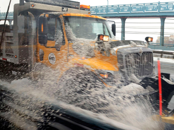 A DRPA plow clears snow on the Ben Franklin Bridge. Traveling through the region was difficult, whether commuters were behind the wheel or trying to use mass transit. (Tom Gralish / Staff Photographer)