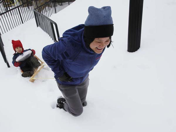 Susan Liu pulls her son James Adams, 3, through snow in Paoli. Her work was closed and his day care was closed. February 13,  2014. ( MICHAEL S. WIRTZ / Staff Photographer )