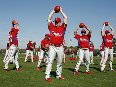 Phillies´ players, including Matt Stairs (center) use medicine balls as they stretch Monday at the Carpenter Complex in Clearwater. (Eric Mencher / Staff Photographer)