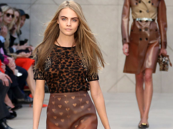 British model Cara Delevingne, left, Model Of The Year at the 2012 British Fashion Awards, wears a design created by Burberry Prorsum, during London Fashion Week, at Kensington Gardens in west London, Monday, Feb. 18, 2013. (Photo by Joel Ryan/Invision/AP)