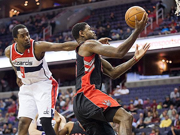 Raptors Amir Johnson drives the ball and scores against Wizards Martell Webster. (Manuel Balce Ceneta/AP)