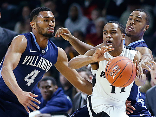 Providence guard Bryce Cotton passes the ball under defensive pressure from Villanova guards Darrun Hilliard II and Tony Chennault during the first half. (Elise Amendola/AP)