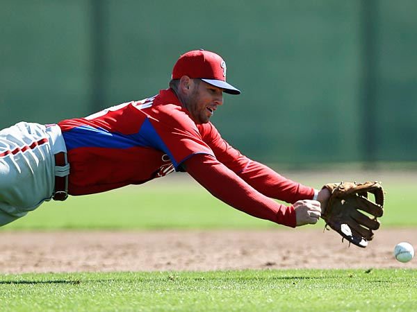 Philadelphia Phillies´ Kevin Frandsen dives for a ball during a workout at baseball spring training on Sunday, Feb. 17, 2013, in Clearwater, Fla. (AP Photo/Matt Slocum)