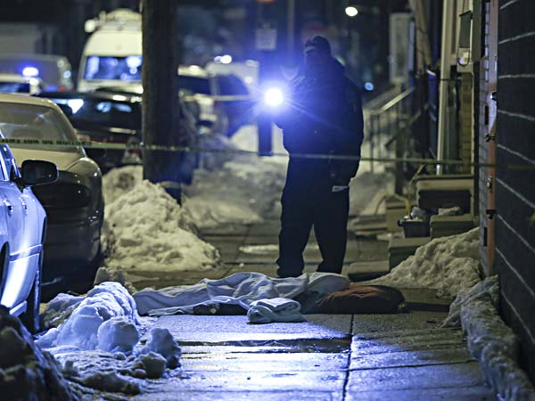 "An ""execution style"" shooting in Olney has left one man dead and another clinging to life tonight, police said. A Crime Scene Police Officer looks over the area where a victim lay on the sidewalk covered with a sheet, Wednesday,  February 19, 2014.  (  Steven M. Falk / Staff Photographer )"