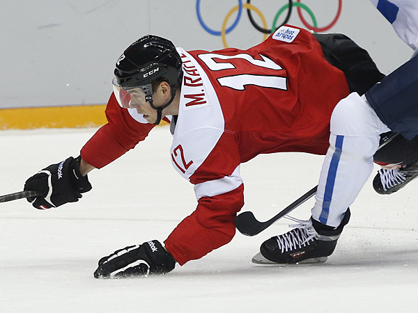 Austria forward Michael Raffl dives for control of the puck against Finland in the first period of a men&acute;s ice hockey game at the 2014 Winter Olympics, Thursday, Feb. 13, 2014, in Sochi, Russia. (Julio Cortez/AP)<br />