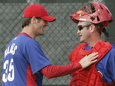 Cole Hamels and catcher Brian Schneider meet after Hamel´s threw a pitching session at Bright House Field on Friday.  (Yong Kim / Staff Photographer)