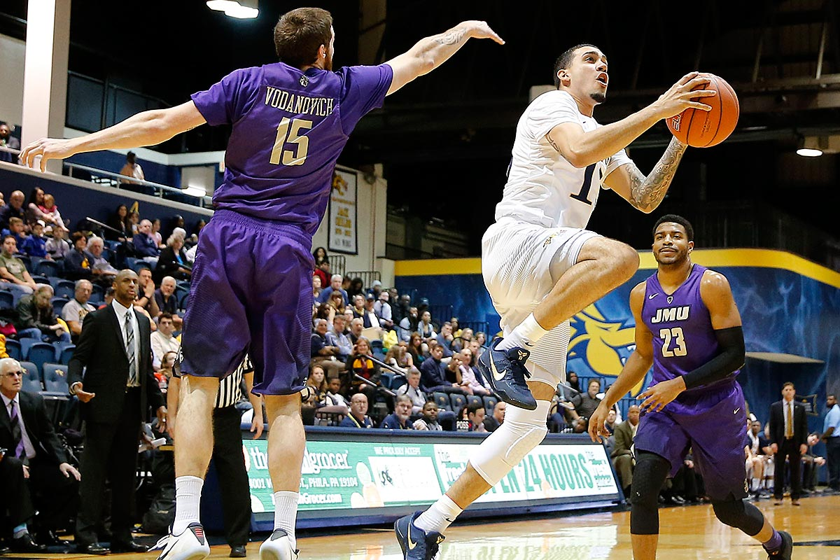 Drexel guard Sammy Mojica drives to the basket past James Madison forward Tom Vodanovich (left) and forward Ramone Snowden (right).