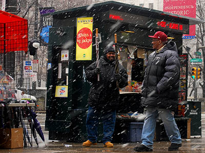 As the snow falls Thursday, Ronnie Murphy sells umbrellas for a bargain price of $3 near the Market Street subway on 15th Street. (Sarah Schu / Staff Photographer)