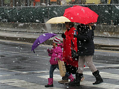 Snow falls at Broad and Race streets as a family scurries through it on Thursday afternoon. (Laurence Kesterson / Staff Photographer)