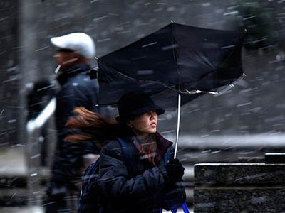 A woman´s umbrella is upset from a gust of wind Thursday during a snow storm in Philadelphia. (AP Photo / Matt Rourke)