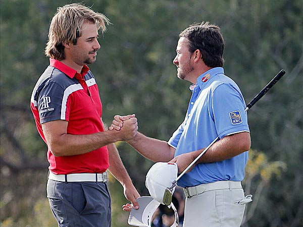 Victor Dubuisson shakes hands with Graeme McDowell after winning on the 18th hole in his match. (Matt York/AP)