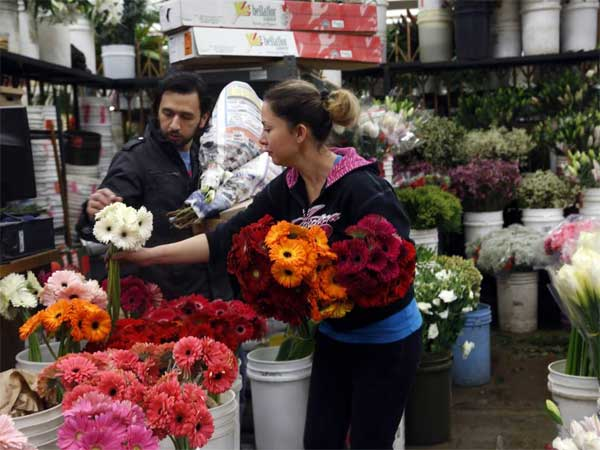 FILE - In this Feb. 14, 2014, photo, buyer Steve Moren, left, examines flowers for purchase for his girlfriend for Valentine´s Day, at the Flower Market in Los Angeles. The Conference Board releases the Consumer Confidence Index for February, on Tuesday, Feb. 25, 2014. (AP Photo/Nick Ut, File)