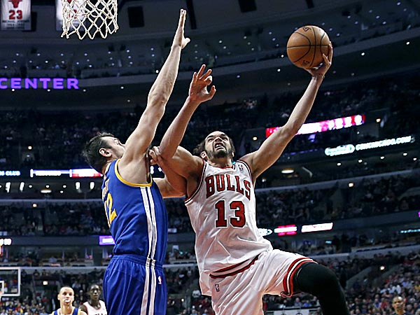 Bulls center Joakim Noah shoots over Warriors center Andrew Bogut. (Charles Rex Arbogast/AP)